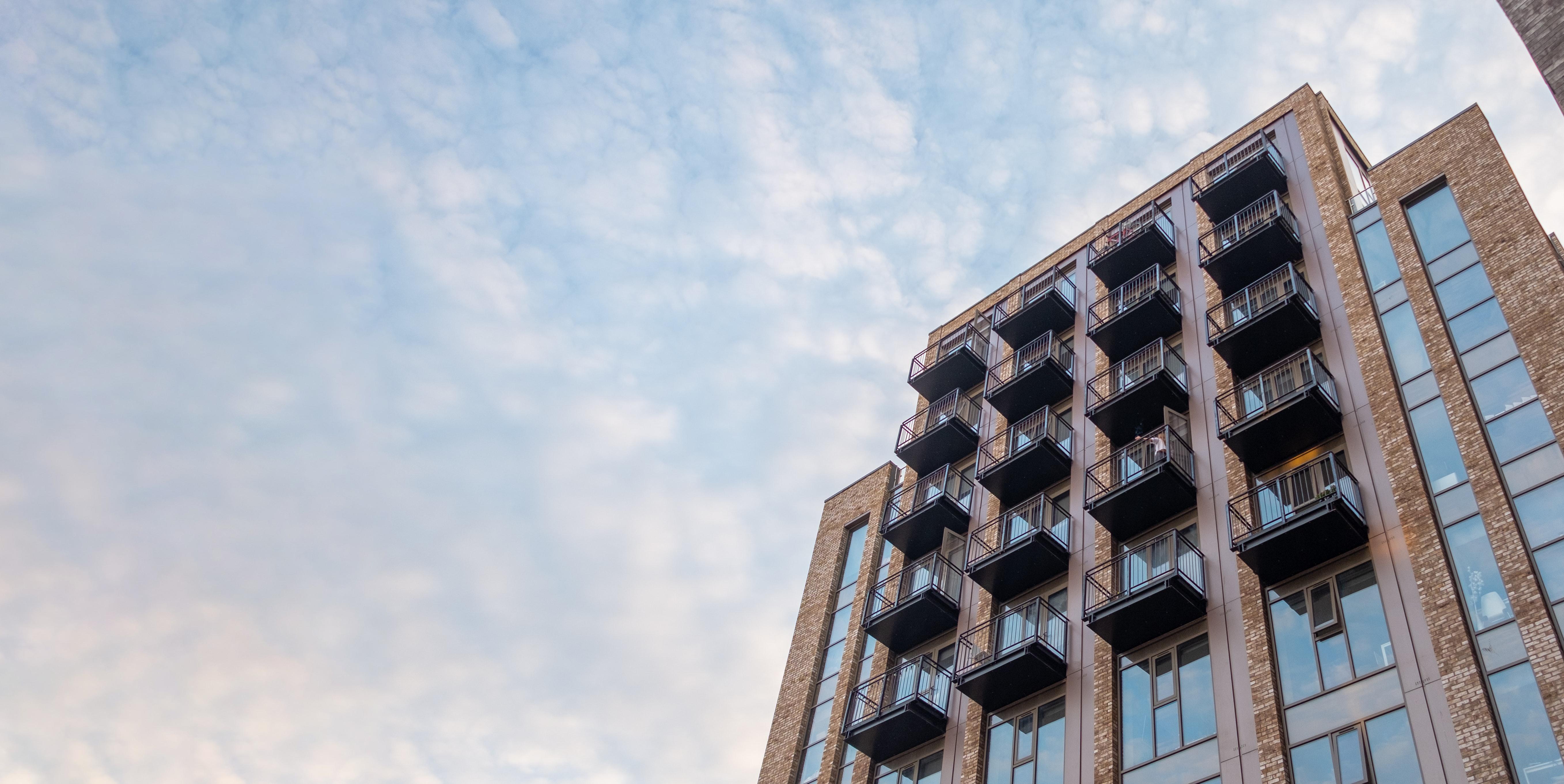 Modernes, sehr schickes Hochhaus mit Blick auf einen blauen Himmel mit ganz leichten Wolken